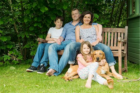 people sitting on bench - Portrait of family with two children sitting on garden bench with dog Stock Photo - Premium Royalty-Free, Code: 649-07238620