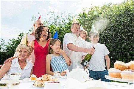 Family celebrating birthday, man opening champagne Stock Photo - Premium Royalty-Free, Code: 649-07238649