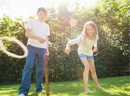 Brother and sister playing hoopla in garden Stock Photo - Premium Royalty-Free, Code: 649-07238643