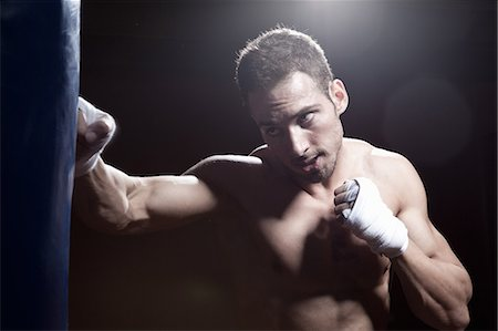 Boxer training with punch bag Stock Photo - Premium Royalty-Free, Code: 649-07238773