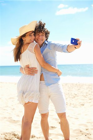 Couple self photographing with mobile phone on beach Stock Photo - Premium Royalty-Free, Code: 649-07238867