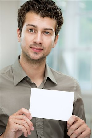 Young man holding white card Stock Photo - Premium Royalty-Free, Code: 649-07238904
