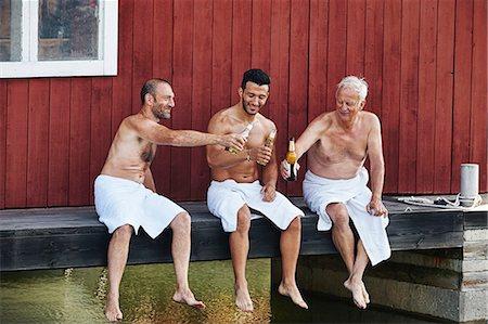 Three men sharing a beer outside sauna Stock Photo - Premium Royalty-Free, Code: 649-07238964