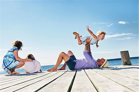 family  fun  outside - Family playing on jetty, Utvalnas, Gavle, Sweden Stock Photo - Premium Royalty-Free, Code: 649-07238978