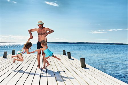 summer - Father and daughters playing on pier, Utvalnas, Gavle, Sweden Stock Photo - Premium Royalty-Free, Code: 649-07238985