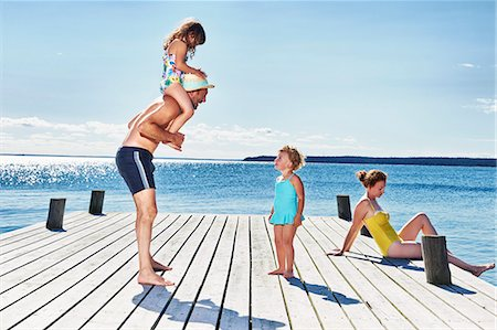 Parents and two young girls on pier, Utvalnas, Gavle, Sweden Stock Photo - Premium Royalty-Free, Code: 649-07238986