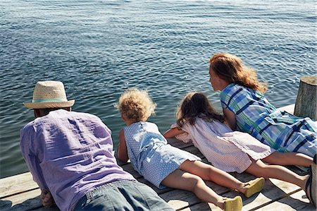 Parents and daughters lying on pier, Utvalnas, Gavle, Sweden Stock Photo - Premium Royalty-Free, Code: 649-07238998