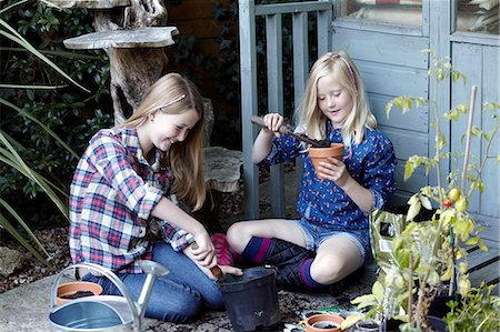 Two girls in garden planting seeds into pots Stock Photo - Premium Royalty-Free, Code: 649-07239021