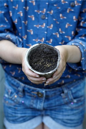 Close up of girl holding flower pot with seeds Stock Photo - Premium Royalty-Free, Code: 649-07239023