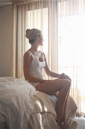 Young woman on bed looking out of window Stock Photo - Premium Royalty-Free, Code: 649-07239044