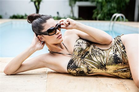Young woman in gold bathing costume at hotel poolside Stock Photo - Premium Royalty-Free, Code: 649-07239071
