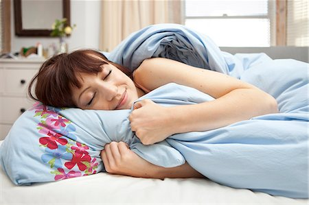 Young woman in bed with eyes closed Stock Photo - Premium Royalty-Free, Code: 649-07239126