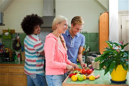 Group of friends preparing vegetables in kitchen Stock Photo - Premium Royalty-Free, Code: 649-07239129