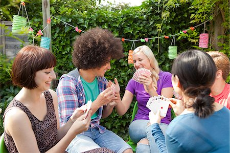Group of young adult friends playing cards in garden Stock Photo - Premium Royalty-Free, Code: 649-07239144