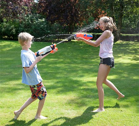 Brother and sister play fighting with water guns in garden Stock Photo - Premium Royalty-Free, Code: 649-07239176