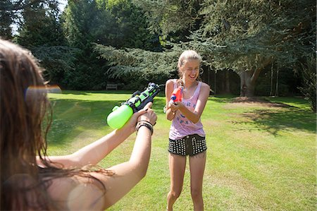 Two teenage girls firing water guns in garden Stock Photo - Premium Royalty-Free, Code: 649-07239177