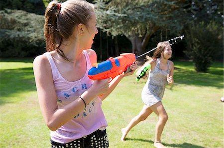 Two teenage girls playing with water guns in garden Stock Photo - Premium Royalty-Free, Code: 649-07239178