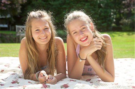 Portrait of two teenage girls lying on picnic blanket Stock Photo - Premium Royalty-Free, Code: 649-07239179