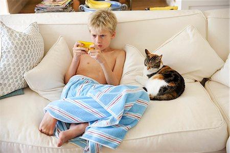 Boy sitting on sofa playing handheld game Stock Photo - Premium Royalty-Free, Code: 649-07239184