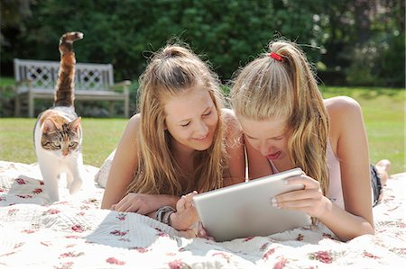 Two teenage girls on picnic blanket looking at digital tablet Stock Photo - Premium Royalty-Free, Code: 649-07239181