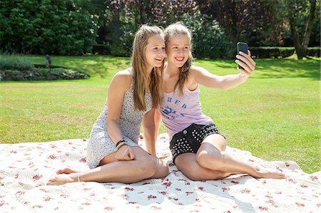Two teenage girls on picnic blanket taking self portrait Stock Photo - Premium Royalty-Free, Code: 649-07239183