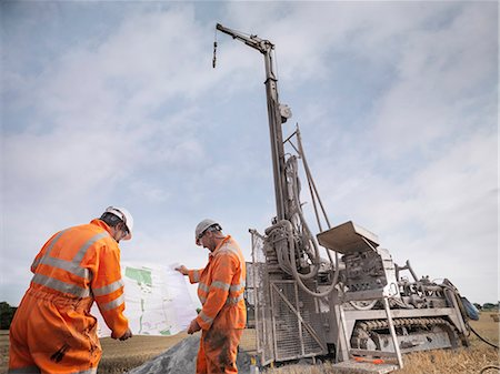 Drilling rig workers inspecting map in field Stock Photo - Premium Royalty-Free, Code: 649-07239192