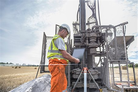 Worker using laptop to survey drilled hole made by drilling rig in field Stock Photo - Premium Royalty-Free, Code: 649-07239207