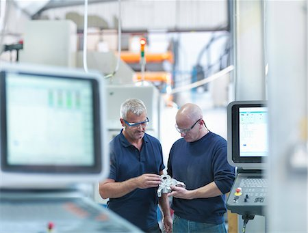 Engineers inspecting complex metal component in factory Stock Photo - Premium Royalty-Free, Code: 649-07239232