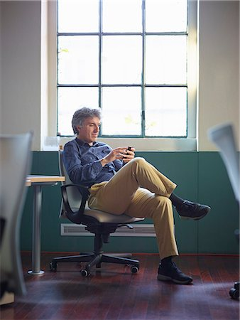 Mature businessman sitting on office chair wit cell phone Stock Photo - Premium Royalty-Free, Code: 649-07239298