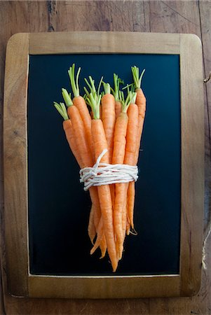 Bunch of carrots on blackboard, still life Stock Photo - Premium Royalty-Free, Code: 649-07239335