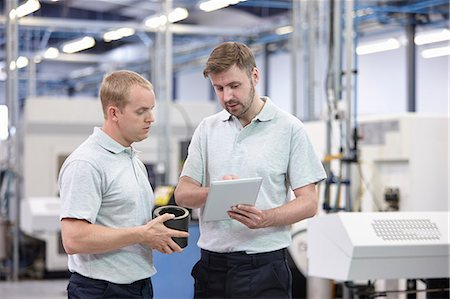 Two workers looking at digital tablet in engineering warehouse Stock Photo - Premium Royalty-Free, Code: 649-07239345