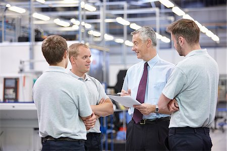 people working in factory - Workers and manager meeting in engineering warehouse Stock Photo - Premium Royalty-Free, Code: 649-07239346