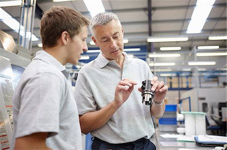 Manager and working looking at component in engineering factory Stock Photo - Premium Royalty-Free, Code: 649-07239350