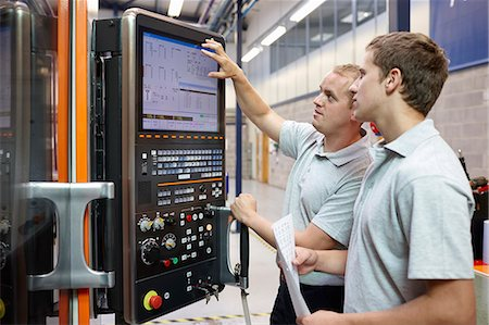 Workers looking at computer monitor in engineering factory Stock Photo - Premium Royalty-Free, Code: 649-07239360