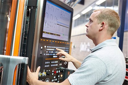 Worker looking at computer monitor in engineering factory Stock Photo - Premium Royalty-Free, Code: 649-07239361