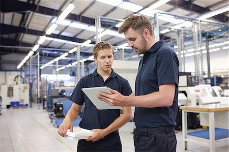 Workers checking order in engineering factory Stock Photo - Premium Royalty-Free, Code: 649-07239371