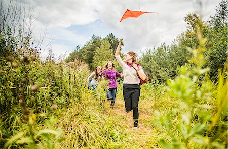 Four young women running through scrubland with kite Stock Photo - Premium Royalty-Free, Code: 649-07239405