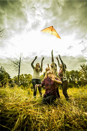 Five young women flying kite in scrubland Stock Photo - Premium Royalty-Free, Code: 649-07239407