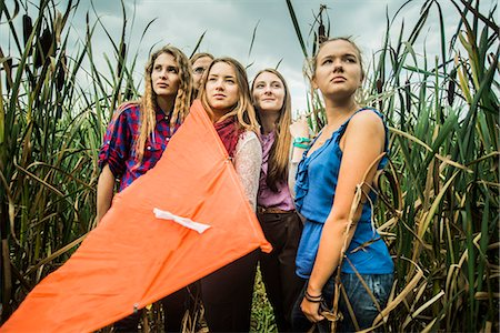 Portrait of five young women in marshes holding kite Stock Photo - Premium Royalty-Free, Code: 649-07239413