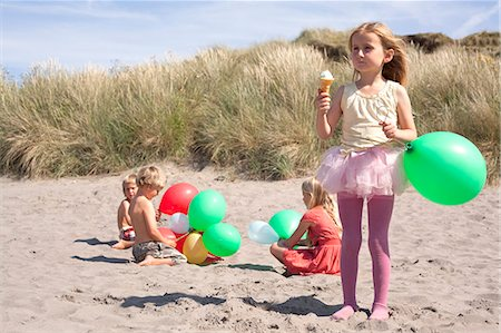 Girl holding balloon eating ice cream on beach, Wales, UK Stock Photo - Premium Royalty-Free, Code: 649-07239464