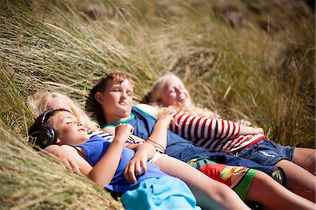 Four friends relaxing in dunes, Wales, UK Stock Photo - Premium Royalty-Free, Code: 649-07239478