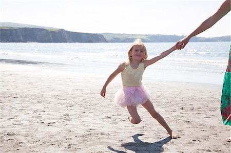 family fun day background - Mother and daughter wearing tutu running on beach, Wales, UK Stock Photo - Premium Royalty-Free, Code: 649-07239471