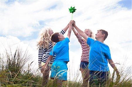 Four friends holding pinwheel, Wales, UK Stock Photo - Premium Royalty-Free, Code: 649-07239480
