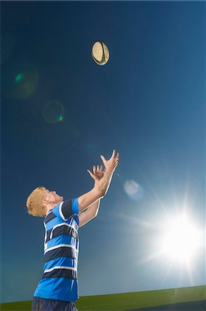 Young man catching rugby ball Stock Photo - Premium Royalty-Free, Code: 649-07239531