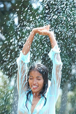 Portrait of young woman in rain with arms raised Stock Photo - Premium Royalty-Free, Code: 649-07239562