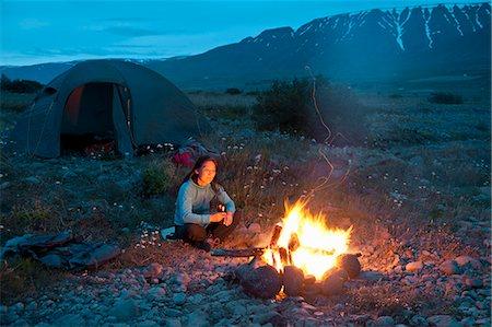 Woman sitting at campfire, Eyjafjordur, North Iceland Stock Photo - Premium Royalty-Free, Code: 649-07239668