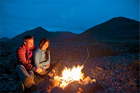 Couple sitting at campfire, Eyjafjordur, North Iceland Stock Photo - Premium Royalty-Free, Code: 649-07239670