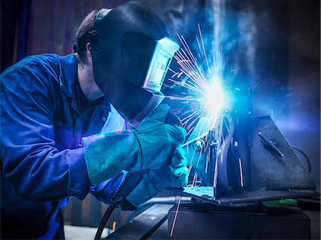 Welder wearing face mask and protective gloves in factory Stock Photo - Premium Royalty-Free, Code: 649-07239695