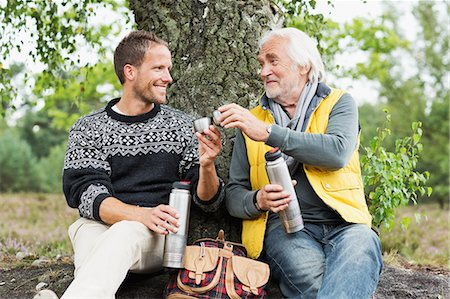 Father and adult son drinking coffee from flask Stock Photo - Premium Royalty-Free, Code: 649-07239758
