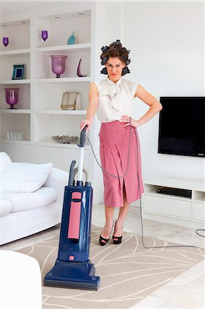 Young woman vacuuming living room Stock Photo - Premium Royalty-Free, Code: 649-07239834